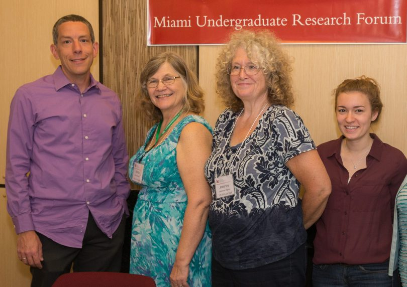 "Office of Research for Undergraduate Director Joe Johnson, Coordinator of Undergraduate Research Martha Weber, and two other personnel stand in front of a banner that reads ""Miami Undergraduate Research Forum."""