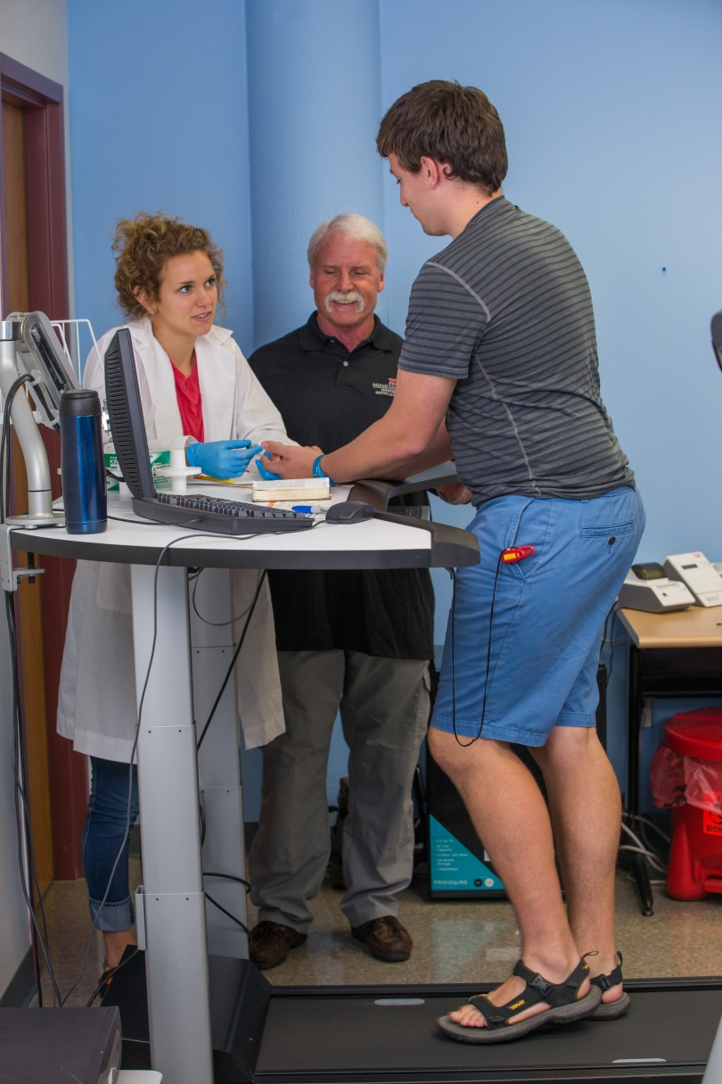 A student researcher takes blood from the finger of a research participant who is walking on a treadmill. The students mentor supervises.