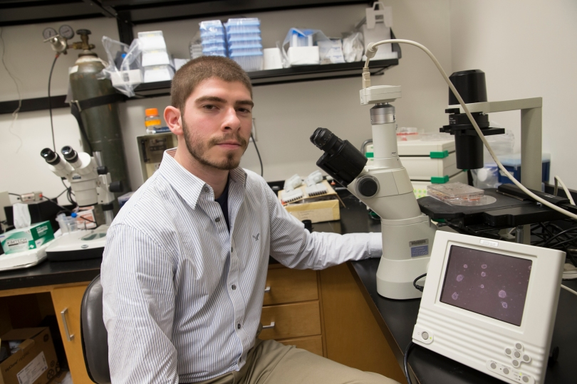 Miami's 2016-2017 Beckman Scholar, Blake Rason, sits at a desk equipped with a microscope.