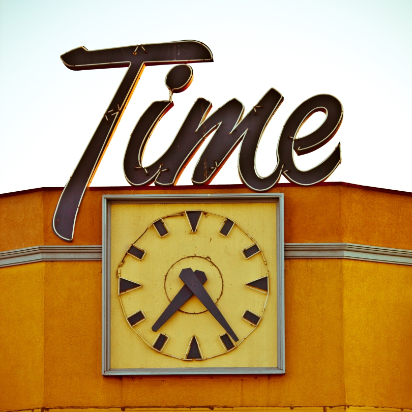Large analog clock on outside of building. The business name -- Time -- is on a neon sign above the clock.