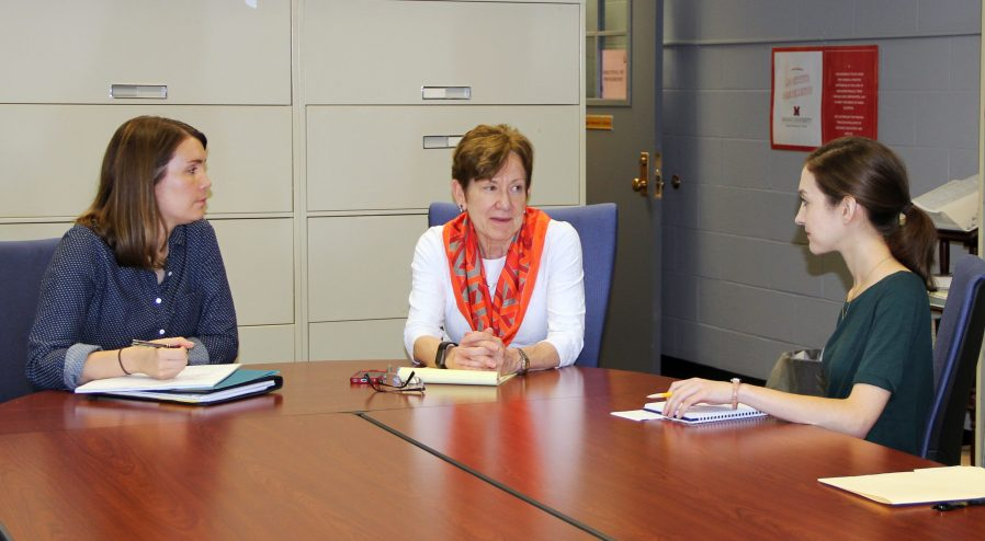 Phyllis Cummins and two doctoral associates have a discussion at a conference table in a library.