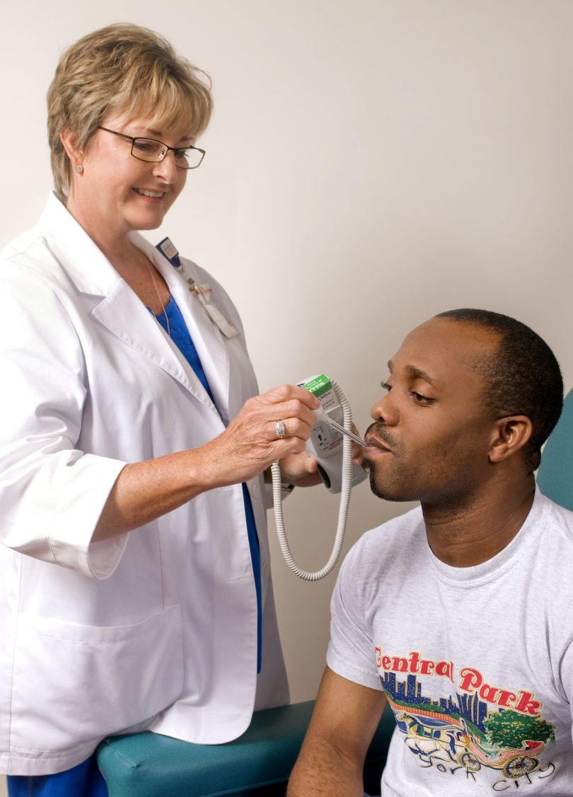 A doctor takes the temperature of a patient.