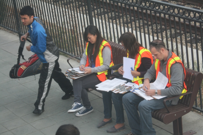 Three people sit on a bench near a railroad track. Each of the people wears and orange vest and holds multiple clipboards and pens. A fourth person, who seems not to be affiliated with the other three is walking away from the bench, presumably after talking to one of the three seated people.