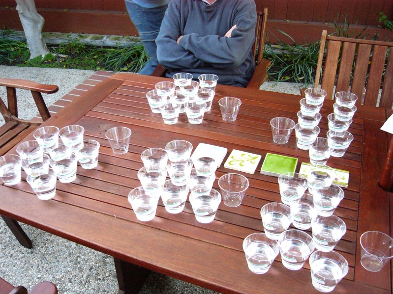 Many cups of water sit on a table. Someone is sitting in one of the chairs pulled up to the table.