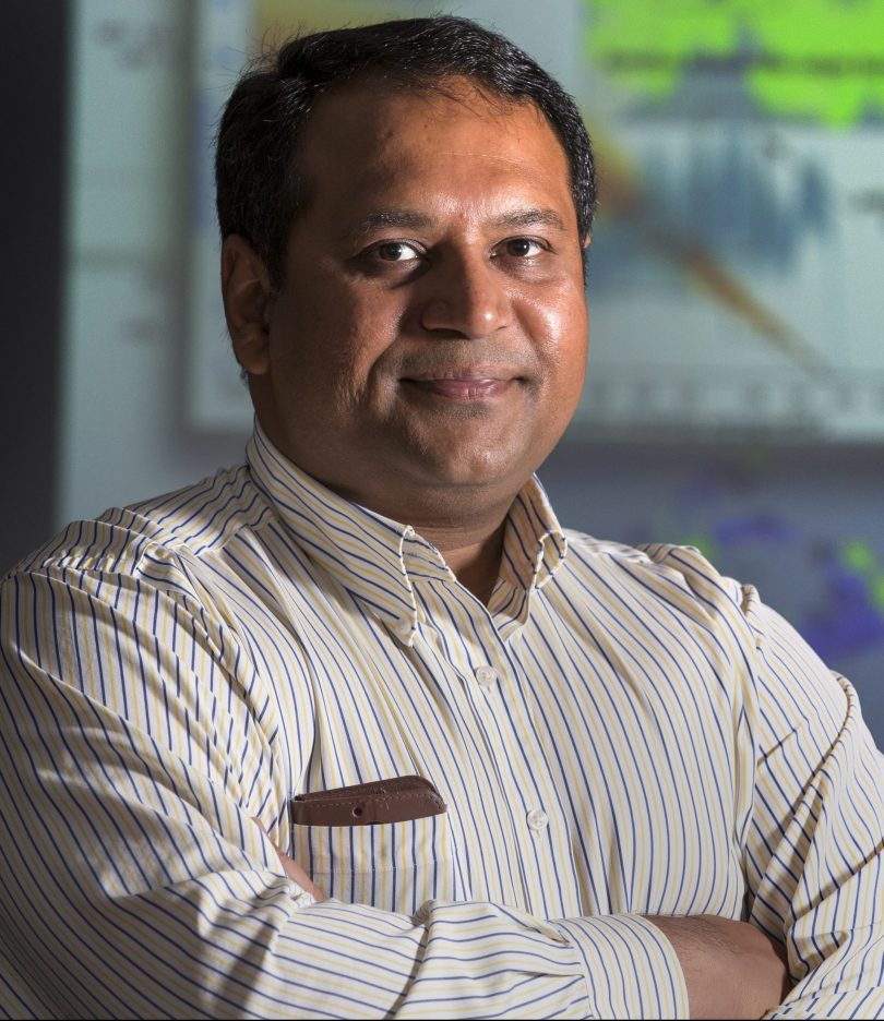"Portrait of Dhananjai ""DJ"" Rao with computer visualizations in the background."
