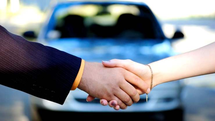 A salesperson and a customer shake hands in front of a car.
