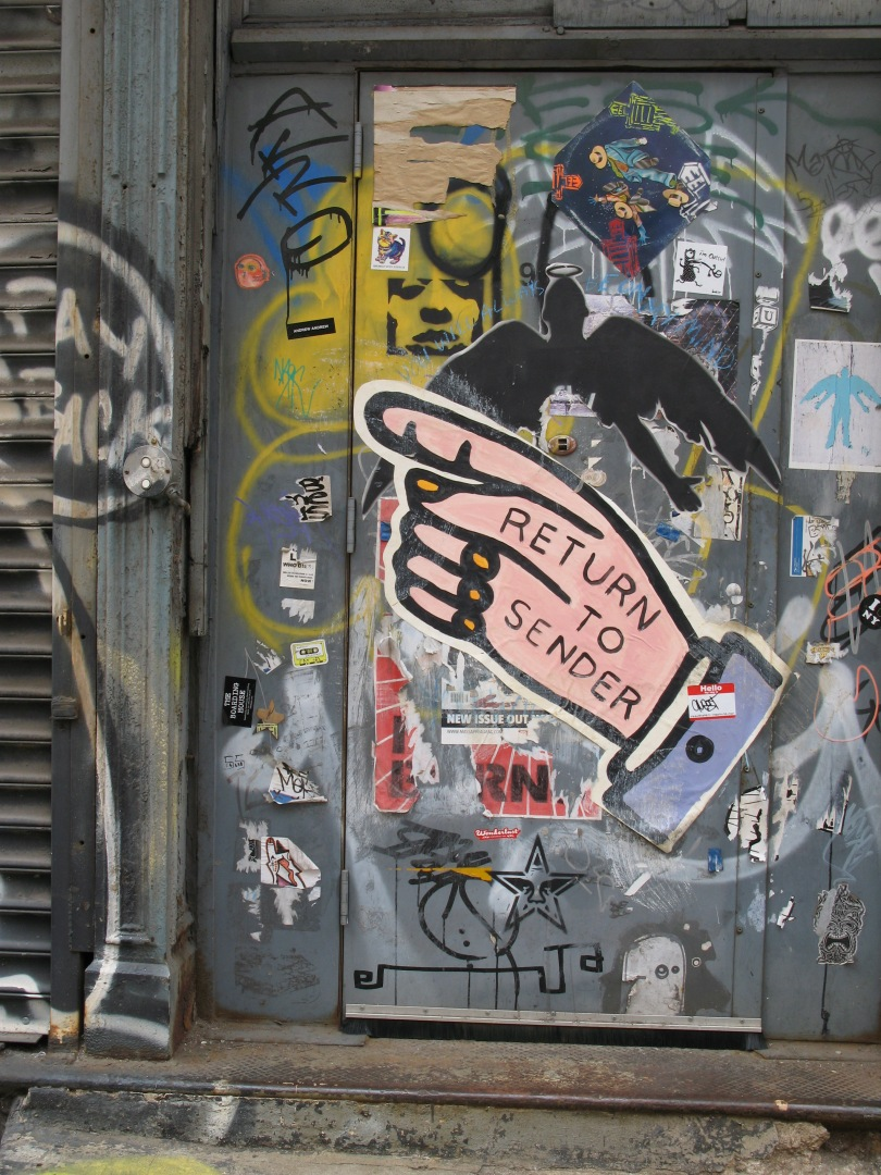 Graffiti on a door. The dominant visual is a hand with a pointing finger. The words Return to Sender are written on the hand.