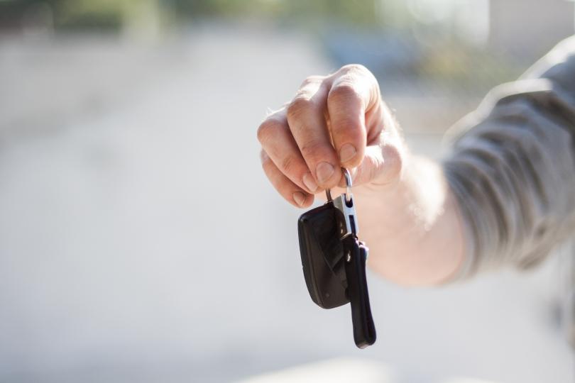 A hand holds a set of car keys.