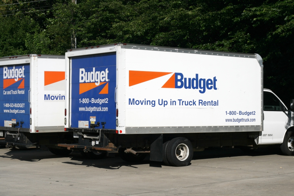 Two Budget rental trucks in a parking lot.