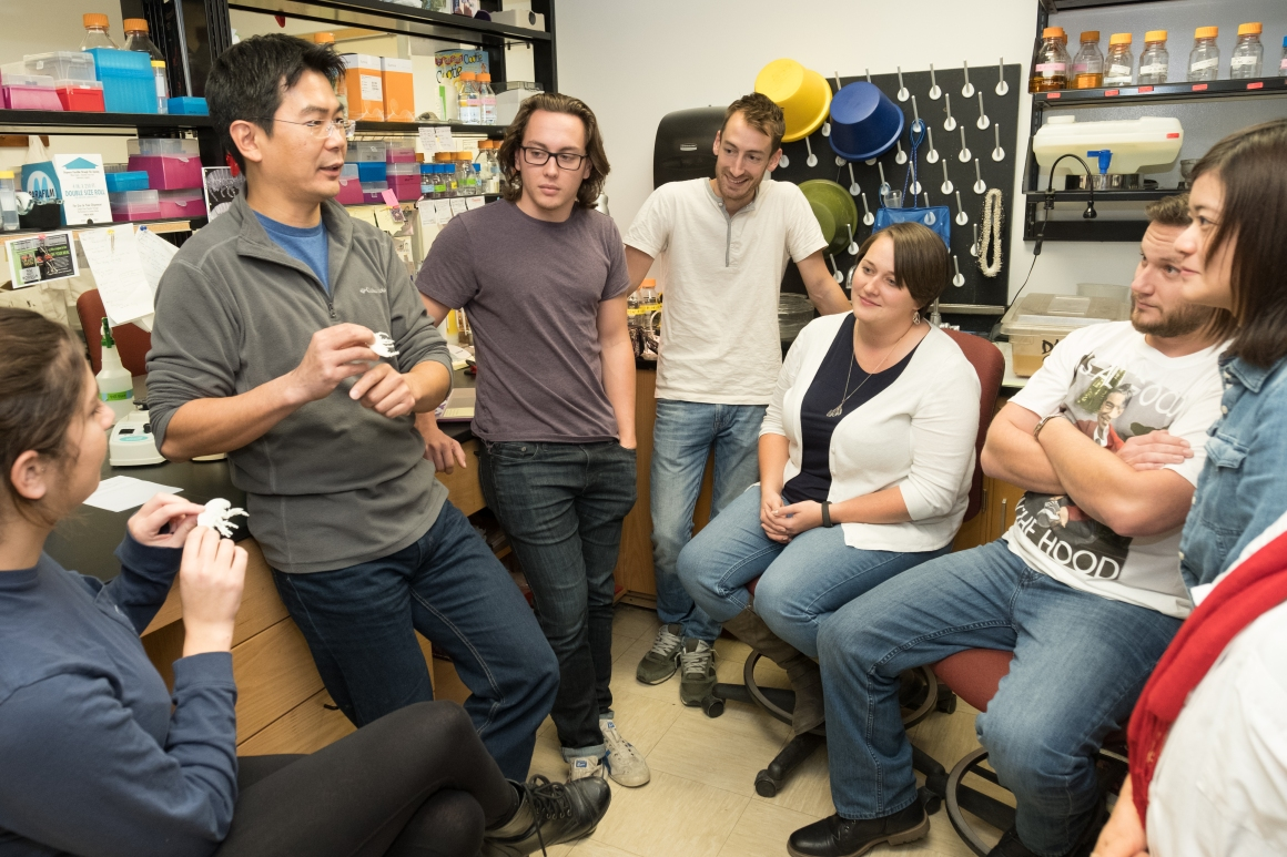 A researcher talks to his lab group, who are gathered around him in a semi-circle.