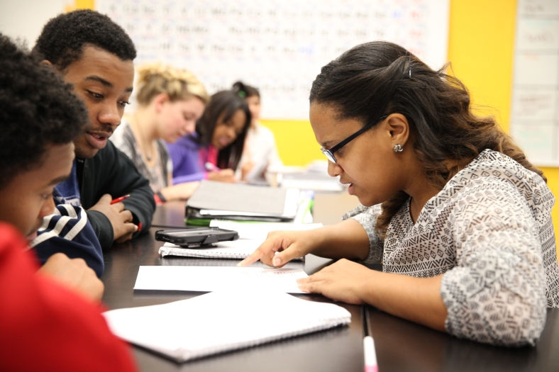 An African-American teacher works with two African-American students in a classroom.