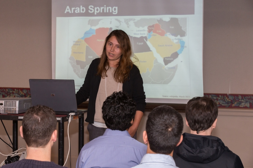 "A woman presents her research to an audience at the Miami University Graduate Research Forum. On the screen behind her is a partial map of north Africa and the Middle East, with the title ""Arab Spring."""