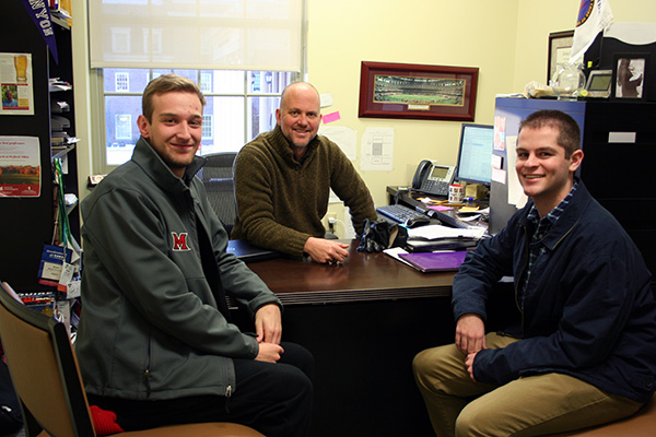 Mike Macey, Rhett Brymer, and Mickey Whitford, gather around the desk in Brymer's Farmer School of Business office.