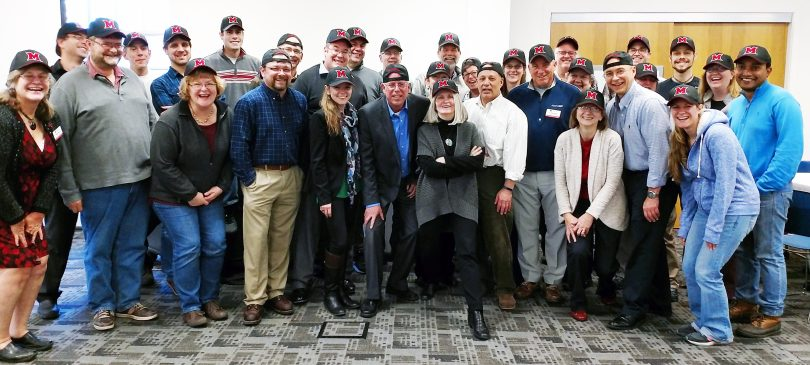 Attendees at OARS 7th Annual Proposals and Awards Reception show of the hats they received from OARS as a token of thanks.