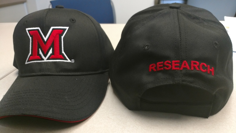 "Two hats, one showing the Miami University ""block M"" logo on the front and the other showing the word ""research"" on the back."