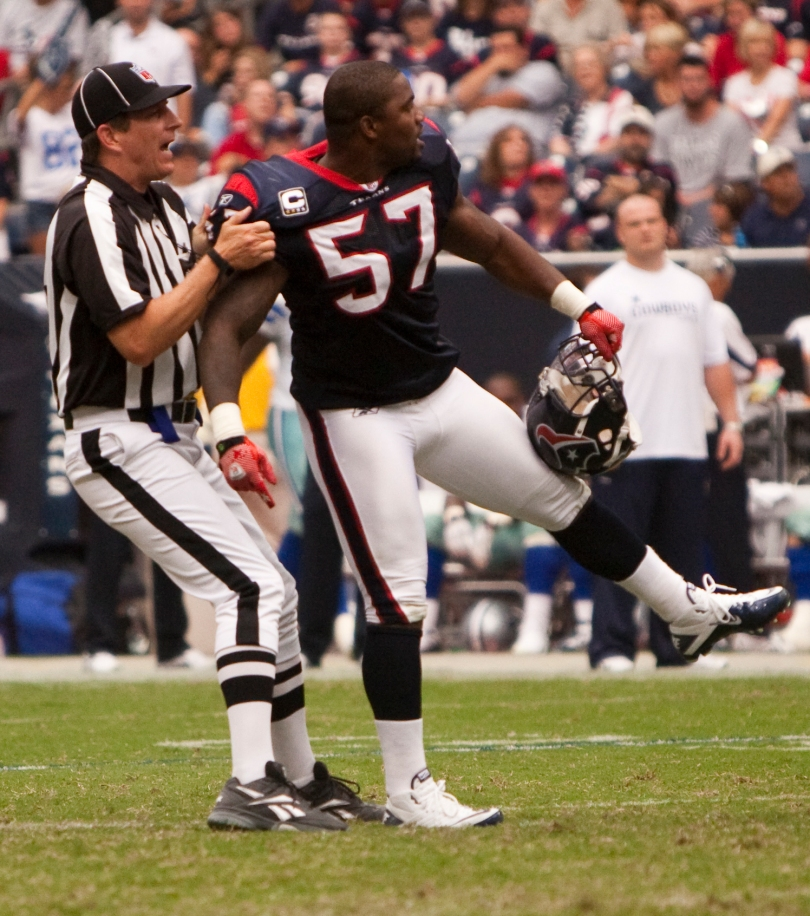 A referee holds back a football player on the field.