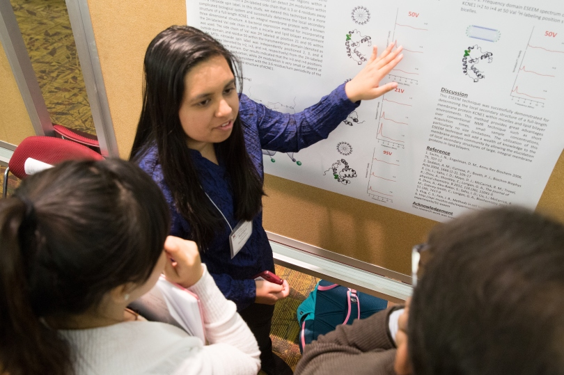 An undergraduate researcher discusses her poster with two attendees at 2016's Undergraduate Research Forum.
