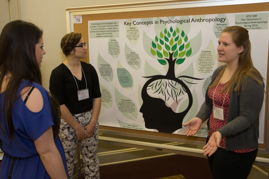 Undergraduate students Olivia Clark and Grace McKittrick stand in front of their Undergraduate Research Forum poster. An unidentified Forum attendee listens as McKittrick explains the poster.