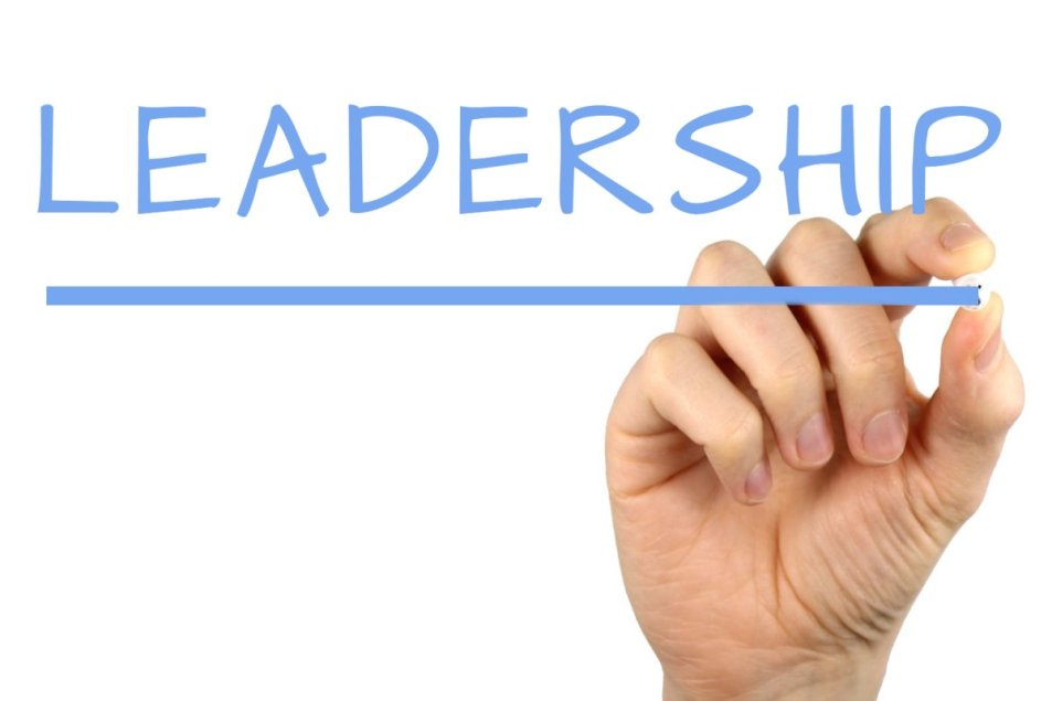 The word Leadership appears to be handwritten by an hand on the backside of a piece of invisible glass. The hand is in the act of underlining the word.