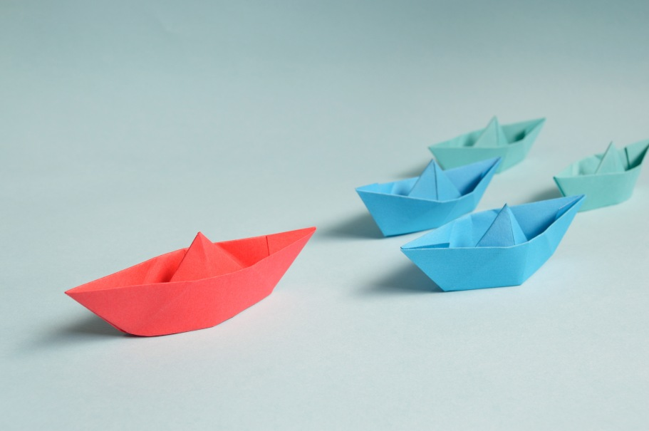 Paper boats on a solid surface. The boat in the lead is larger and a different color than the following boats.