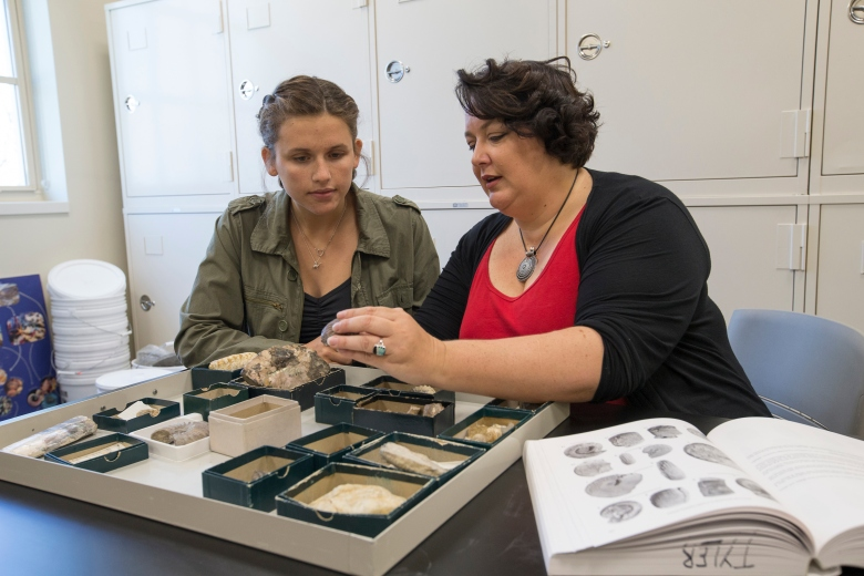 Hannah Kempf and Carrie Tyler look at rock samples and a reference book together.