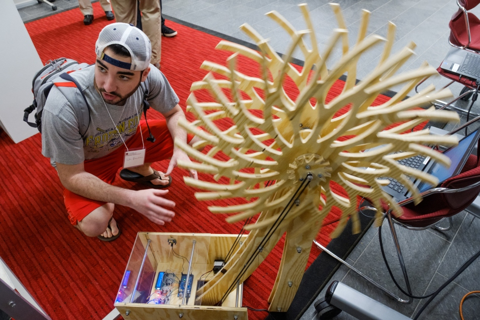 At the Undergraduate Research Forum, a student crouches next to the kinetic sculpture built by Clayton Musloff, Greg Heinrich, and Ruben Victoria.