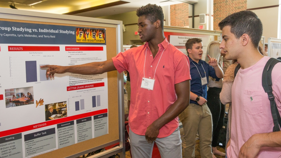 Psychology major Terry Reid (left) explains his team's research to an Undergraduate Research Forum attendee. The title of the poster is readable: Group Studying vs. Individual Studying. The First Year Research Experience (FYRE) logo is also visible.
