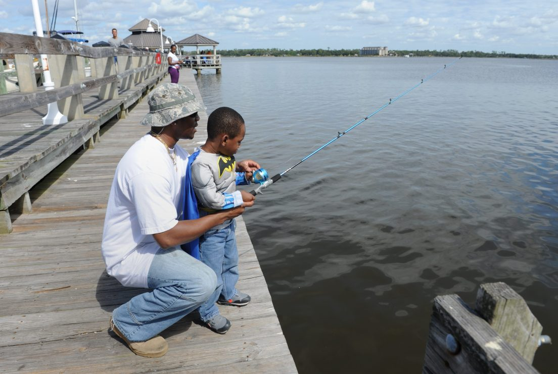 A man crouches behind a little boy, showing him how to use the fishing pole he holds.