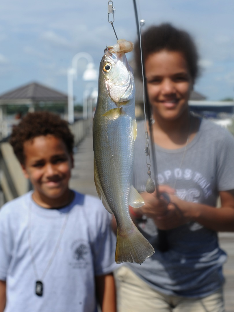 Two children display a fish they caught, which is still on the line on their fishing pole.