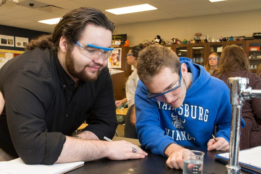 A teacher and a student in a science lab look at the measurement of liquid in a beaker.