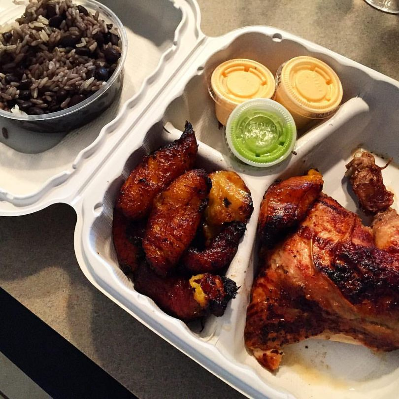 A carryout food box containing a chicken quarter, fried plantains, a bowl of black beans and rice, and three souflee cup containers of sauce (two orange, one green).