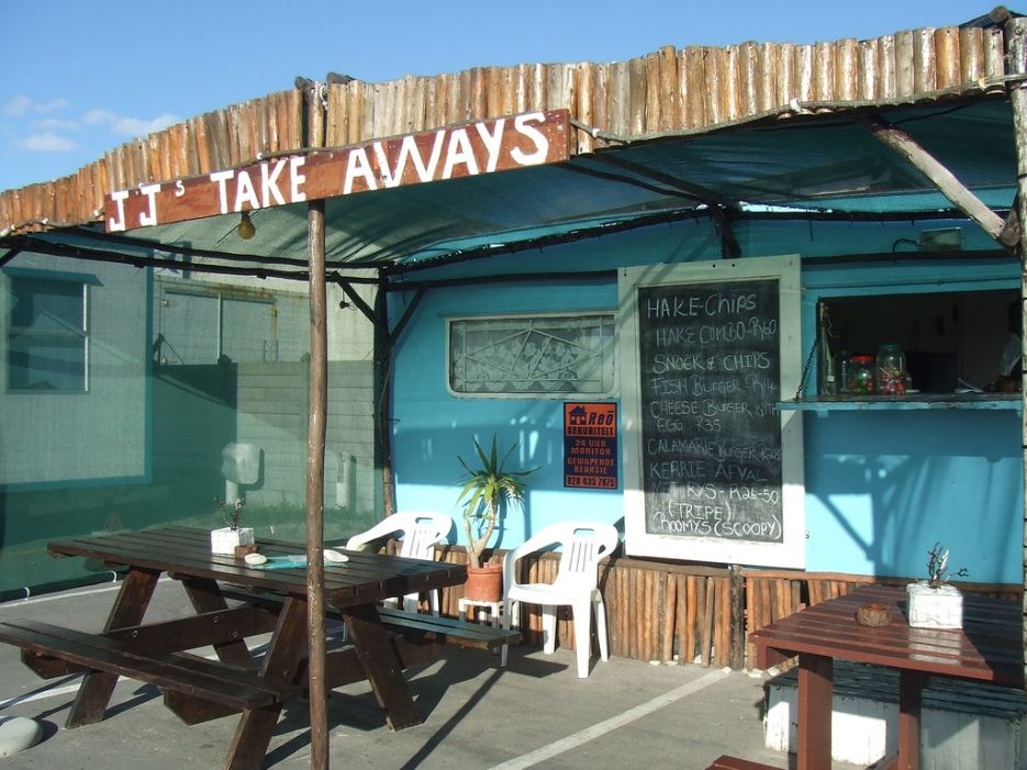 "A trailer that has been outfitted as a take-away restaurant. There is a sign reading ""JJ's Take Aways"" on the awning over a small seating area directly in front of the trailer. The posted menu reads as follows: Hake Chips. Hake Combo - R60. Snack & Chips. Fish Burger R14. Cheese Burger with Egg - R35. Calamarie [sic] burger - R28. Kerrie Afval Met Rys - R26-50 (Tripe). Roomys (Scoopy)."