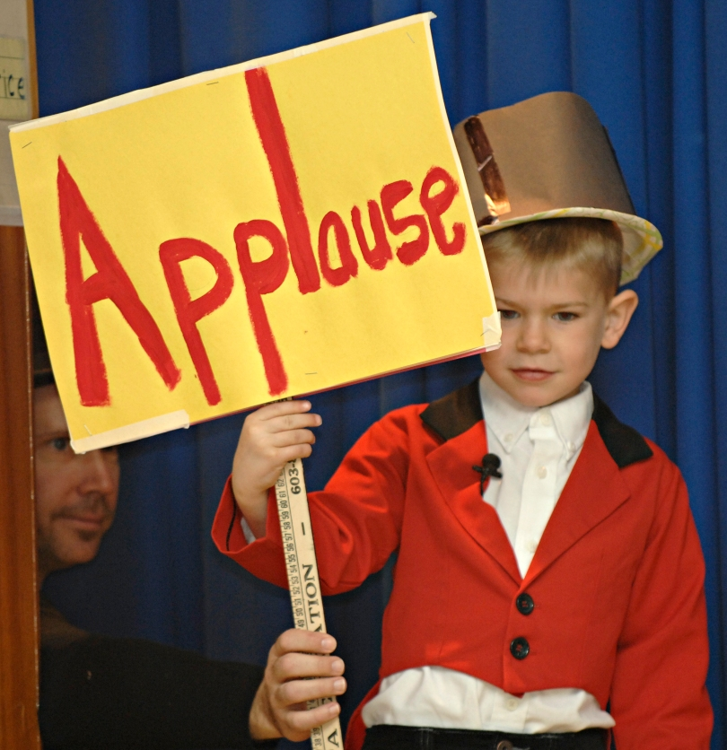 Boy in a ringmaster costume holds up an applause sign with a little help from his teacher