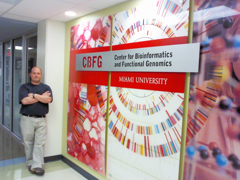 Director Andor Kiss poses by the sign for the Center for Bioinformatics and Functional Genomics (CBFG)