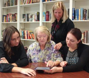 A speech pathology and audiology clinic client uses and iPad with text-to-speech capability, with the help of Kelly Knollman-Porter and two students.