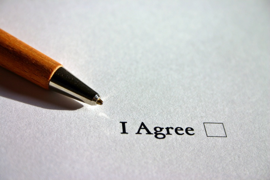 "A pen lies on a piece of paper next to the printed words, ""I Agree,"" and a checkbox."
