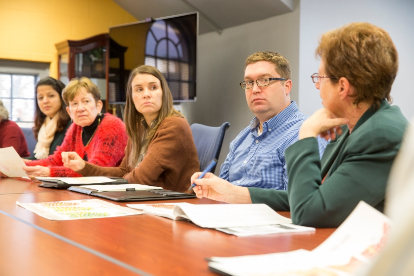 Five researchers have a discussion while seated at a conference table.
