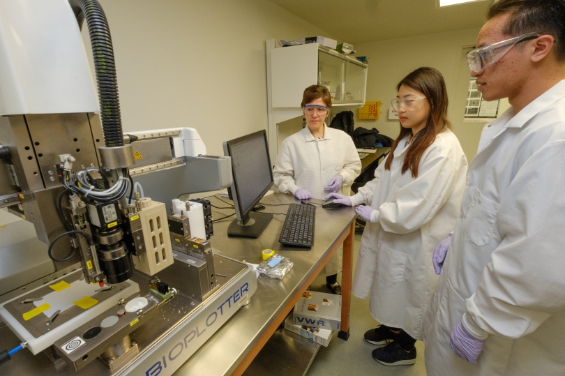 Amy Yousefi, Songmi Koo, and Junyi Liu are gathered around a computer and bioplotter in Yousefi's lab.
