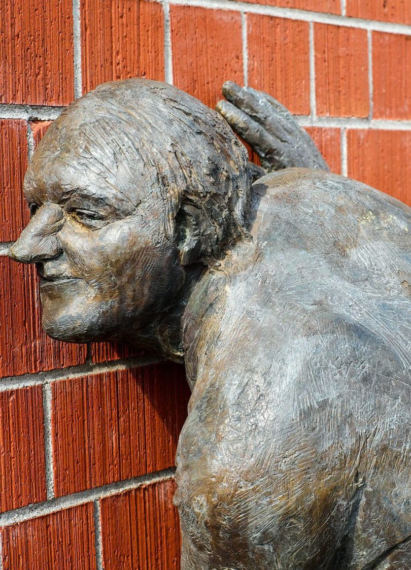 Bronze sculptures of a person with their ear pressed up against a brick wall, as though listening.