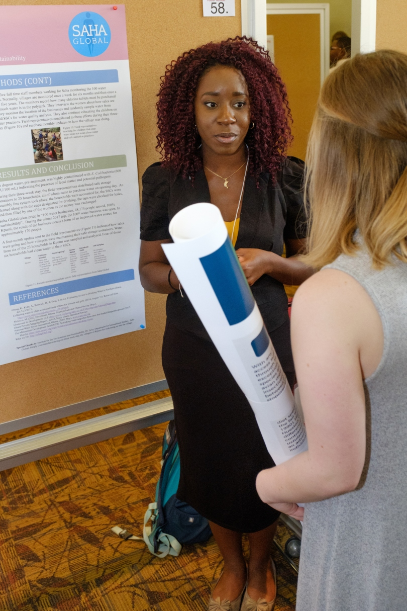 A student presenter discusses her poster with a forum attendee. The SAHA Global logo is visible on the student's poster.