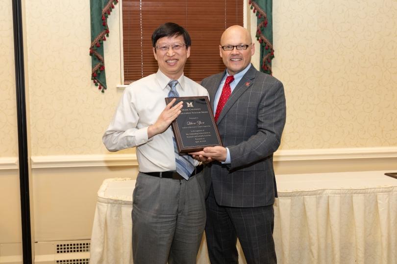 Qihou Zhou and Greg Crawford pose with the plaque commemorating Zhou's Distinguished Scholar Award.