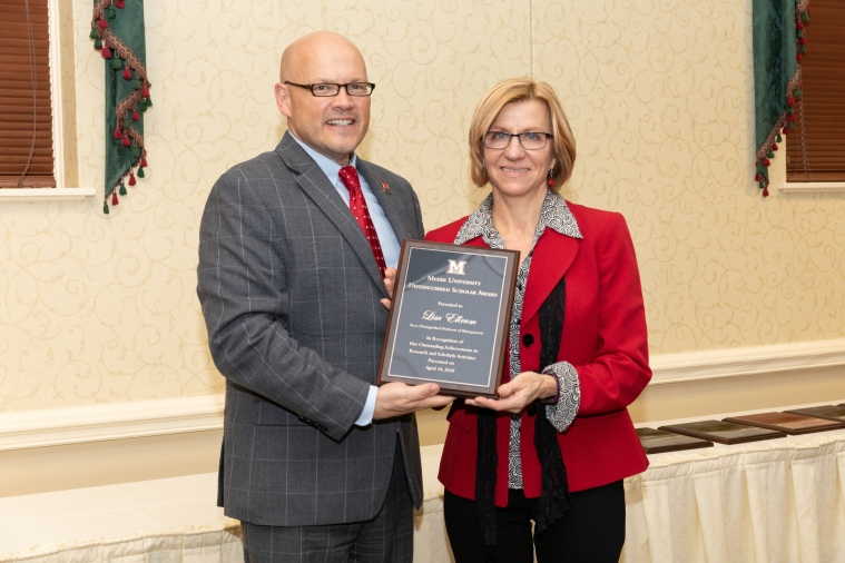 Greg Crawford and Lisa Ellram pose with the plaque commemorating Ellram's Distinguished Scholar Award.