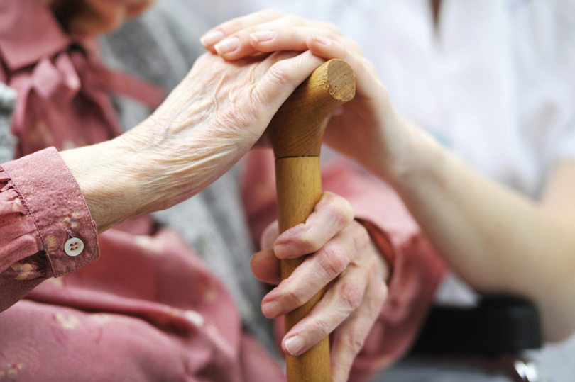 A young woman places her hand over the hand of an older woman holding a cane.