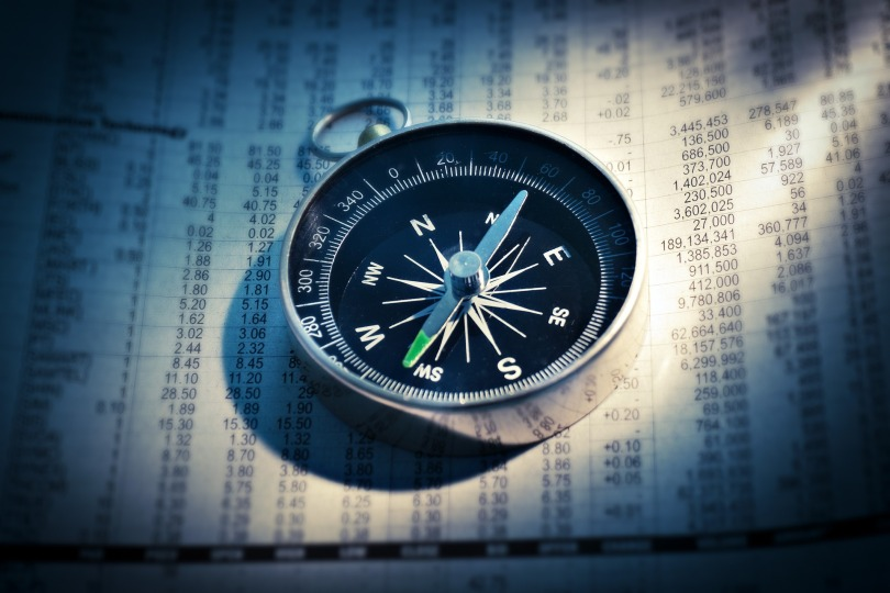 A compass sits on a page of financial information.