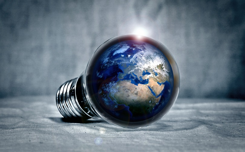 Photo illustration of the earth inside an illuminated lightbulb.