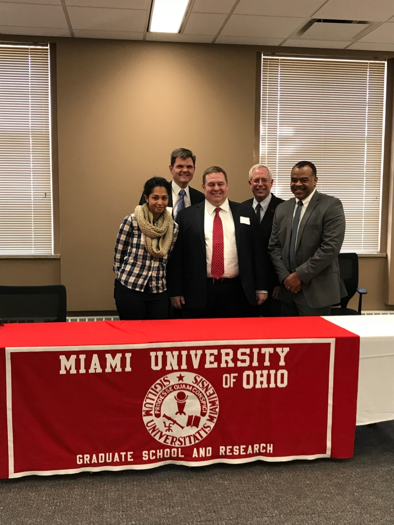 Panelists Candice Matthews, John Leland, Matt Willenbrink, Jim Oris, and Darrin Redus pose behind a table with a Miami University of Ohio Graduate School and Research tablecloth.
