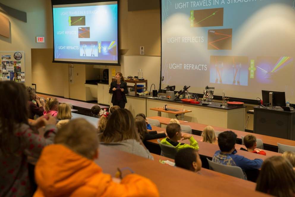 "Professor Burcin Bayram stands at the front of a lecture hall. First graders fill the student seats. Various science instruments are arranged on a table behind Bayram. The projection screens behind her have pictures of light traveling through various media. They are labeled: ""Light Travels in a Straight Line,"" ""Light Reflects,"" and ""Light Refracts."""
