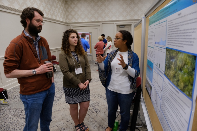 "Ashley Mickens, a junior majoring in environmental earth science sustainability and minoring in history, discusses her poster, ""Changes in Phytoplankton Community Composition Following Simulated Storm Events,"" with two URF attendees."