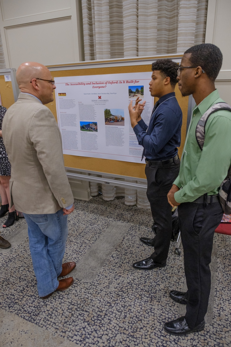 "Aaron Davidson-Bey (center) and Tone Pryer (right) discuss their poster, ""The Accessibility and Inclusion of Oxford: Is It Built for Everyone?"" with Miami University president, Greg Crawford (left)"