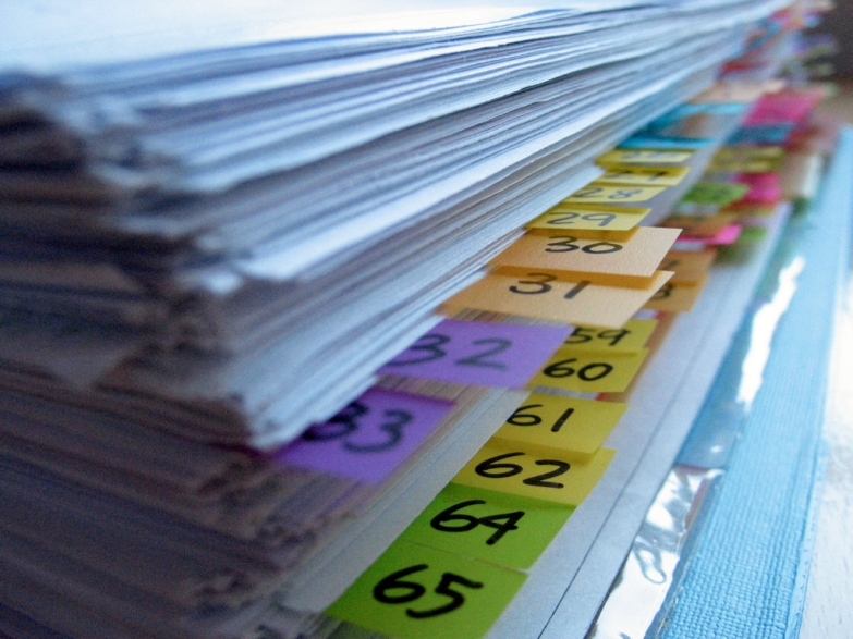 A stack of papers, organized with multi-colored, numbered sticky tabs.